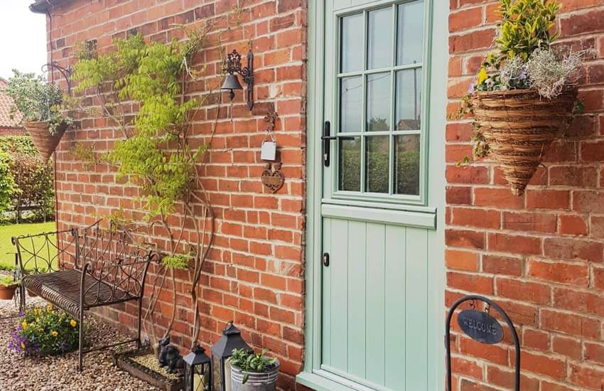 Chartwell green stable door in a red brick extension