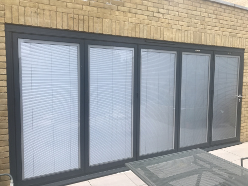 Black bifolding doors with integral blind